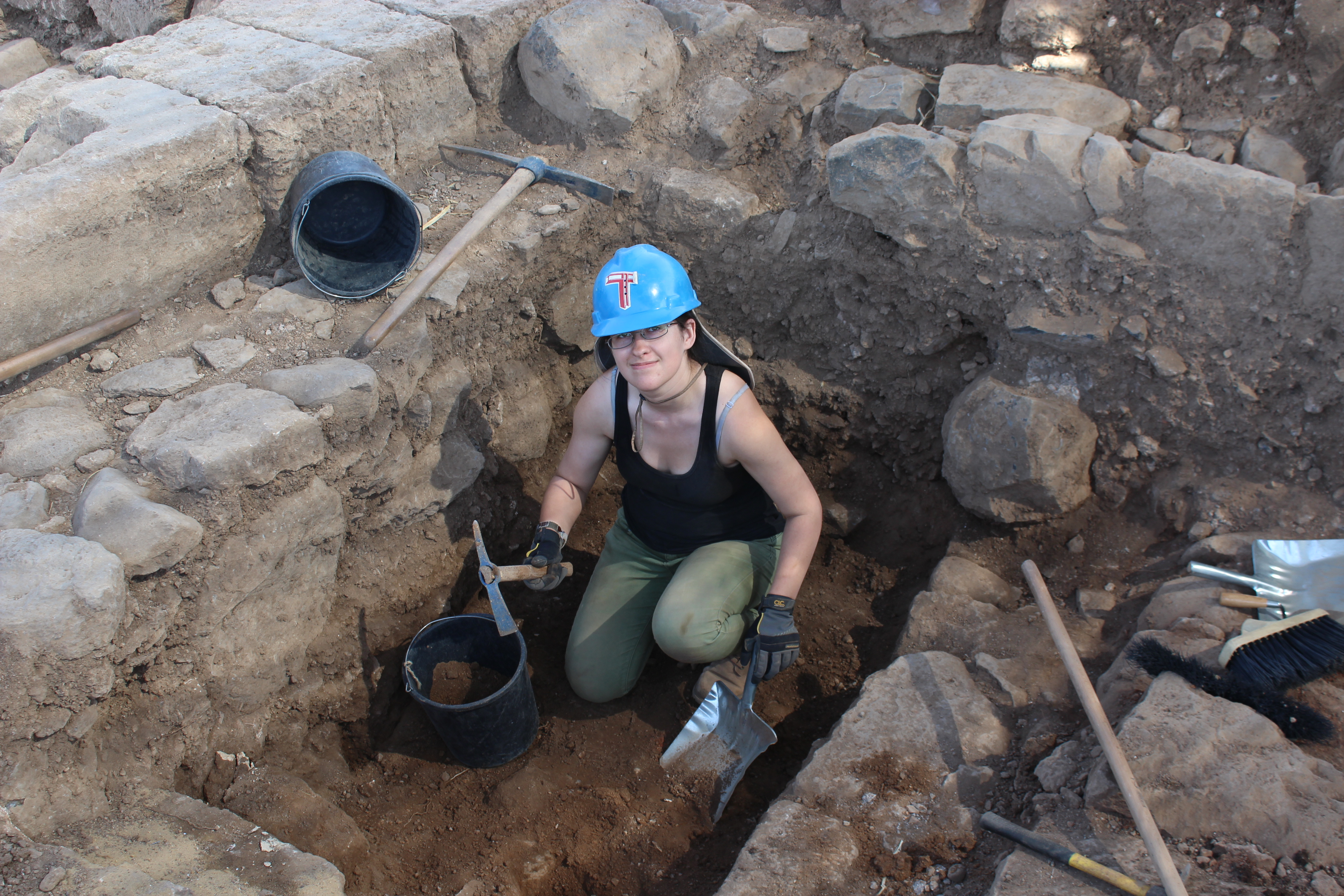 a young girl wearing a blue hard hat digs in an archealogical site in Israel