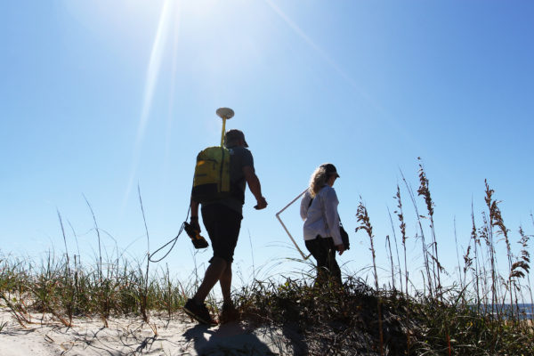 Laura Moore and Peter Ruggiero bring their equipment to undeveloped natural dunes of Fort Macon State Park.