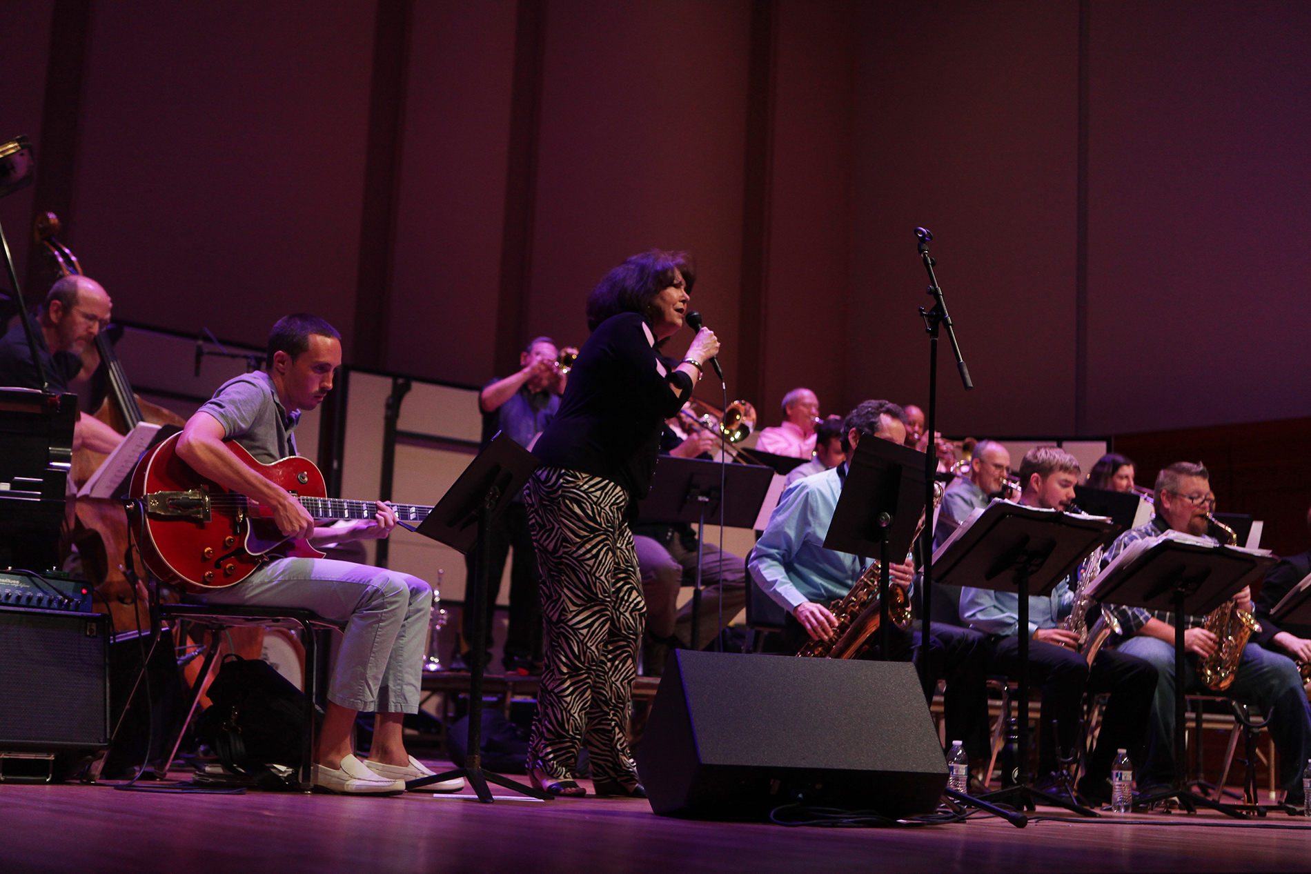 a woman sings on stage at a jazz concert