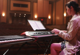 a young girl plays the piano