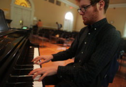 A young man plays the piano
