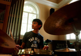 a young boy plays the drums