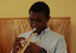 a young man plays the trumpet