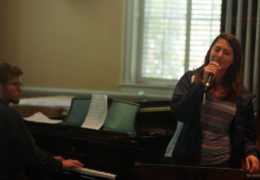 a young woman sings into a microphone