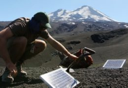 Tim Ronan, an incoming graduate student in the department of geological sciences at UNC, burries a cable connecting a seismometer to a solar panel on the Llaima volcano.Photo by Mary Lide Parker
