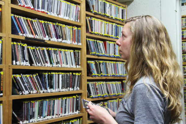 a girl with blond hair stares at a shelf packed with CDs