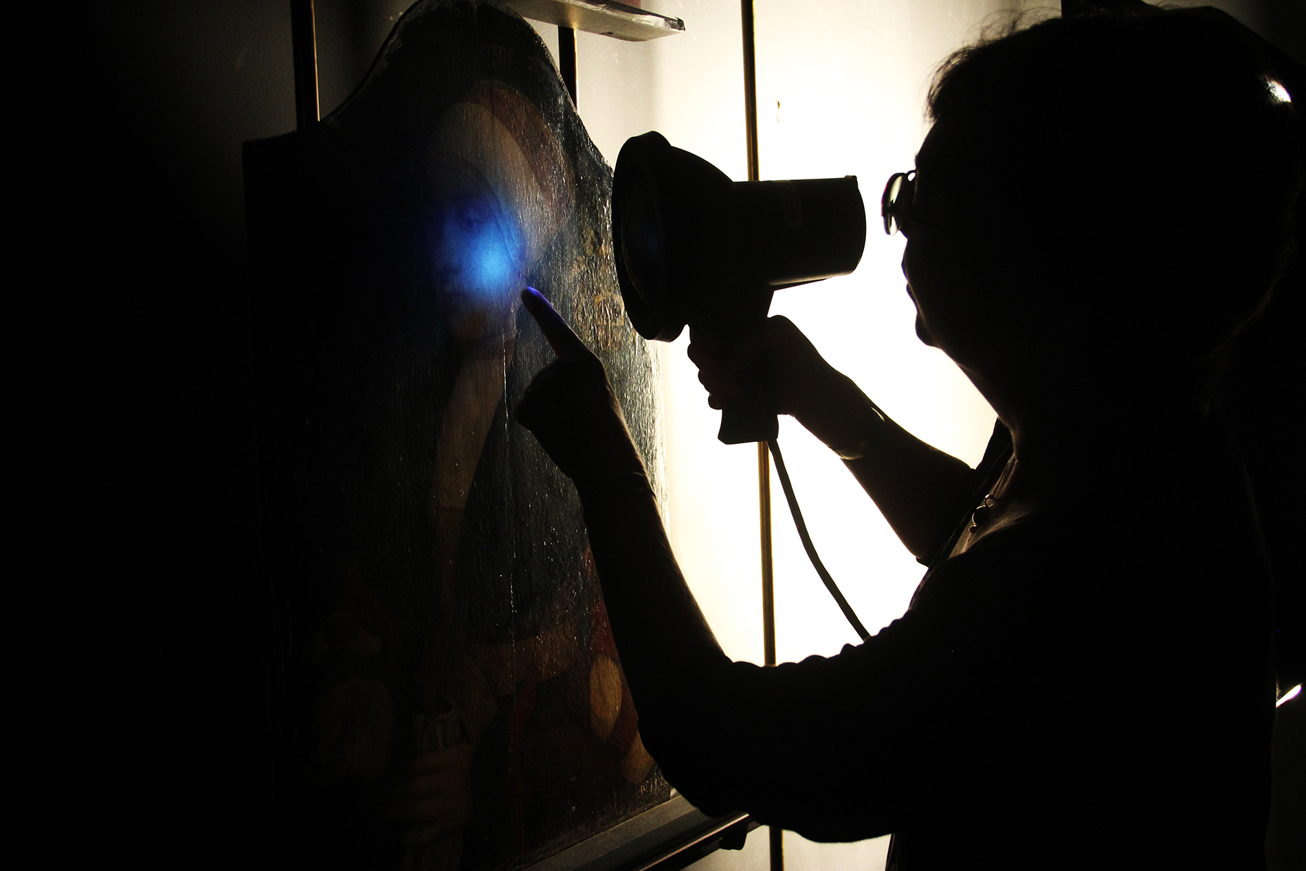 woman shines blacklight on a painting