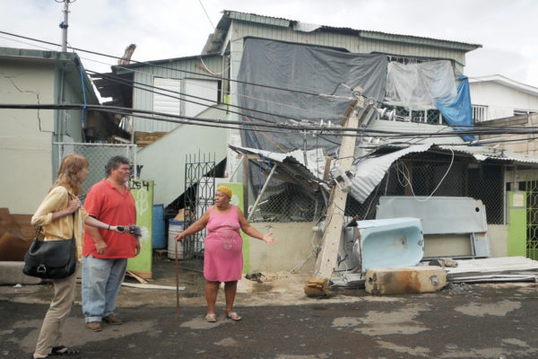 Sandy Smith-Nonini interviews a Puerto Rican woman standing in front of her destroyed home