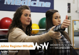 a female exercise and sport scientist holds a girls hand in front of her face to check and checks her balance