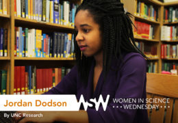a young African-American woman works on her laptop in a library