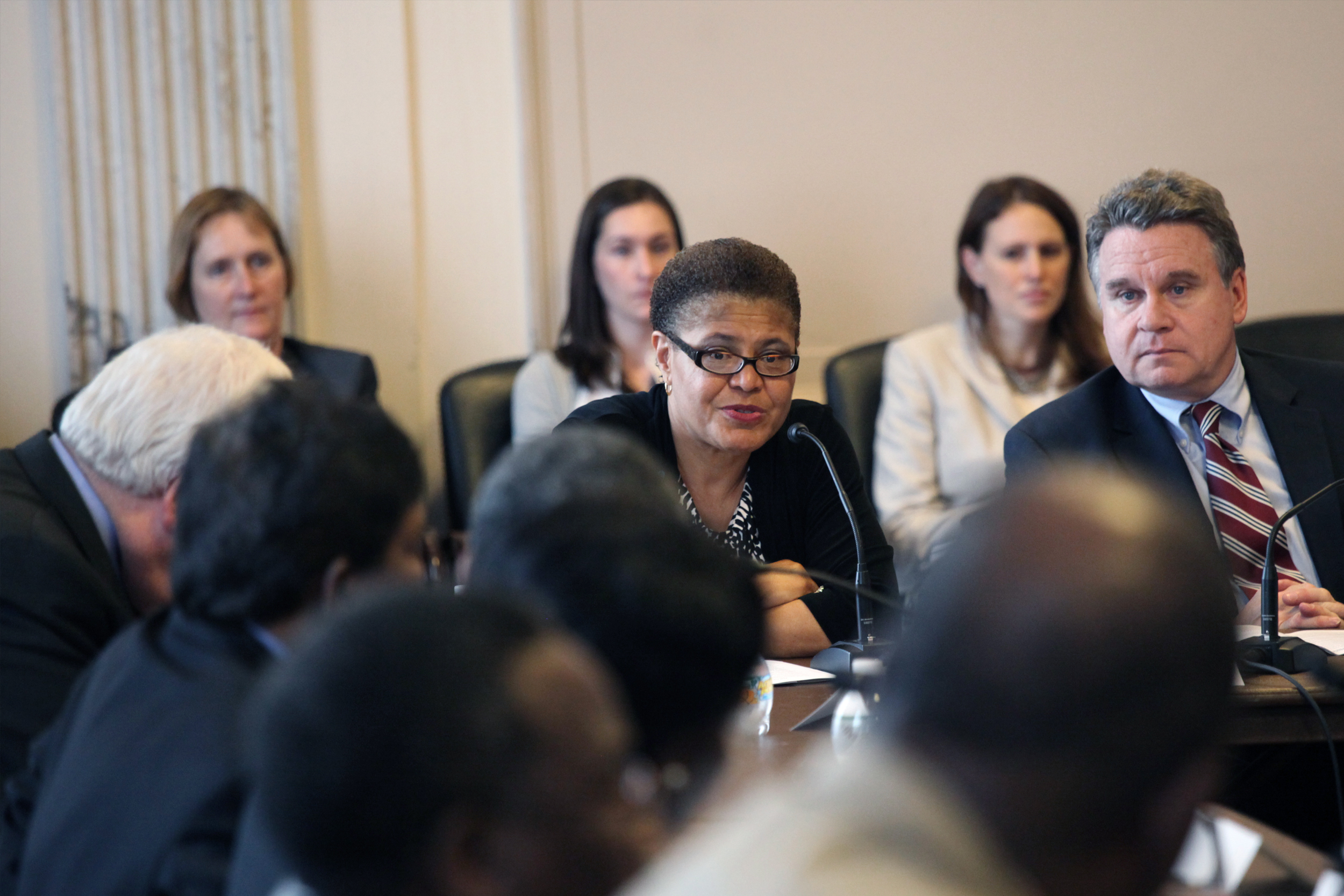 Karen Bass sits at a table surrounded by people