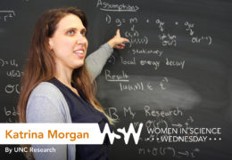 a 20-something woman points to mathematical equations on a chalkboard
