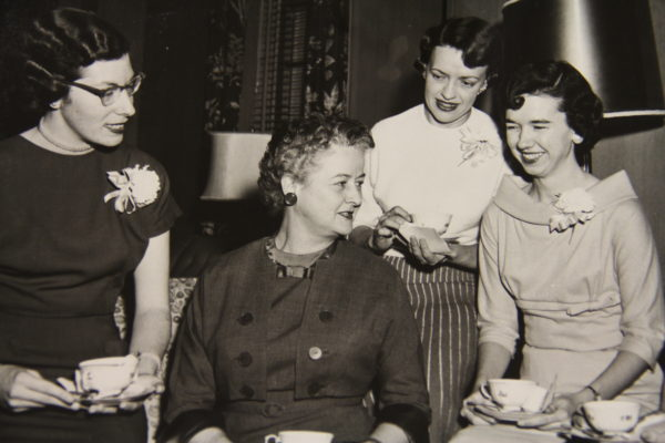 Dean Kemble (second from left) drinks tea with members of a graduating class from the late 1950s.