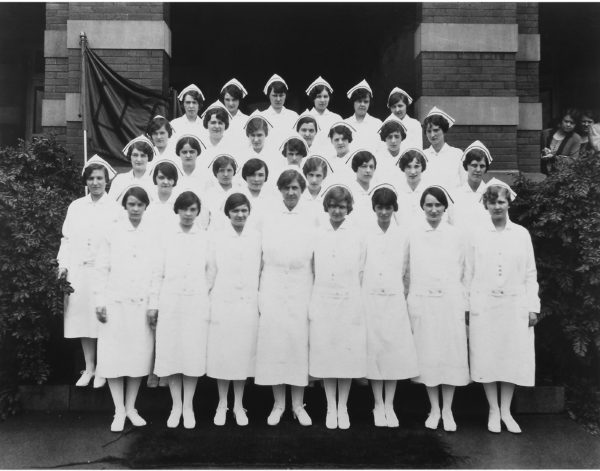 Nurse Kemble stands among her class of nurses in full white apparel, with the traditional nurses cap.