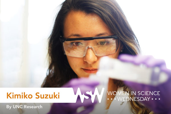 a young Asian woman in chemistry googles pours a solution from one beaker into another