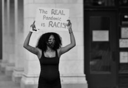 """a woman holds a sign that reads """"the real pandemic is racism"""""""
