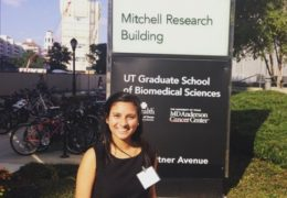 Meaghan Nazareth poses in front of the MD Anderson Cancer Center - Mitchel Research Building sign.
