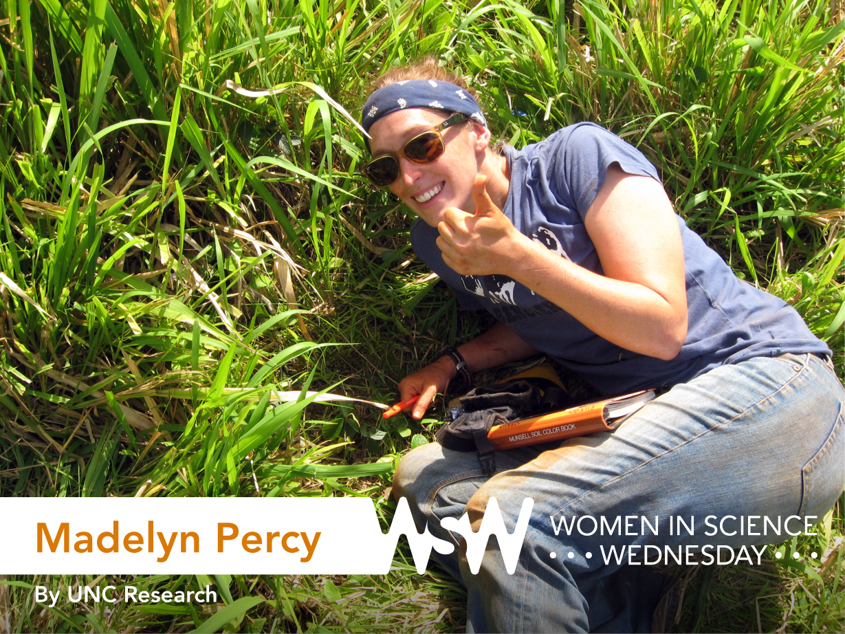 Photo of Madelyn Percy giving a thumbs up as she measures soil drainage on the Galapagos Islands.