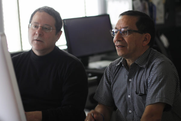 Mario Ruiz (right) and Jonathan Lees discuss acoustic waves recorded from their infrasound equipment.