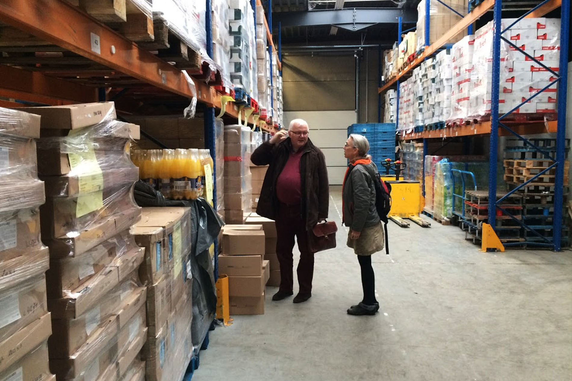 a woman talks with a male food bank official as they stand in a warehouse among shelves of canned food