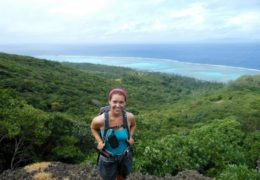 Fisher hiking in Batiki, Fiji, during her gap semester, she poses and smiles at the camera as they over look the ocean.