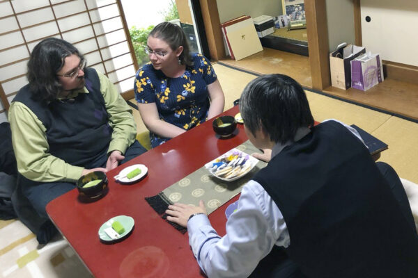 Timothy Smith and his wife sit across the table from a Tenrikyo practitioner