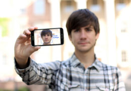 """Patrick Seelinger holds up his phone, showing his face to the camera is a blue box around it with the words """"Patrick Seelinger"""" next to it, indicating the it recognizes him"""