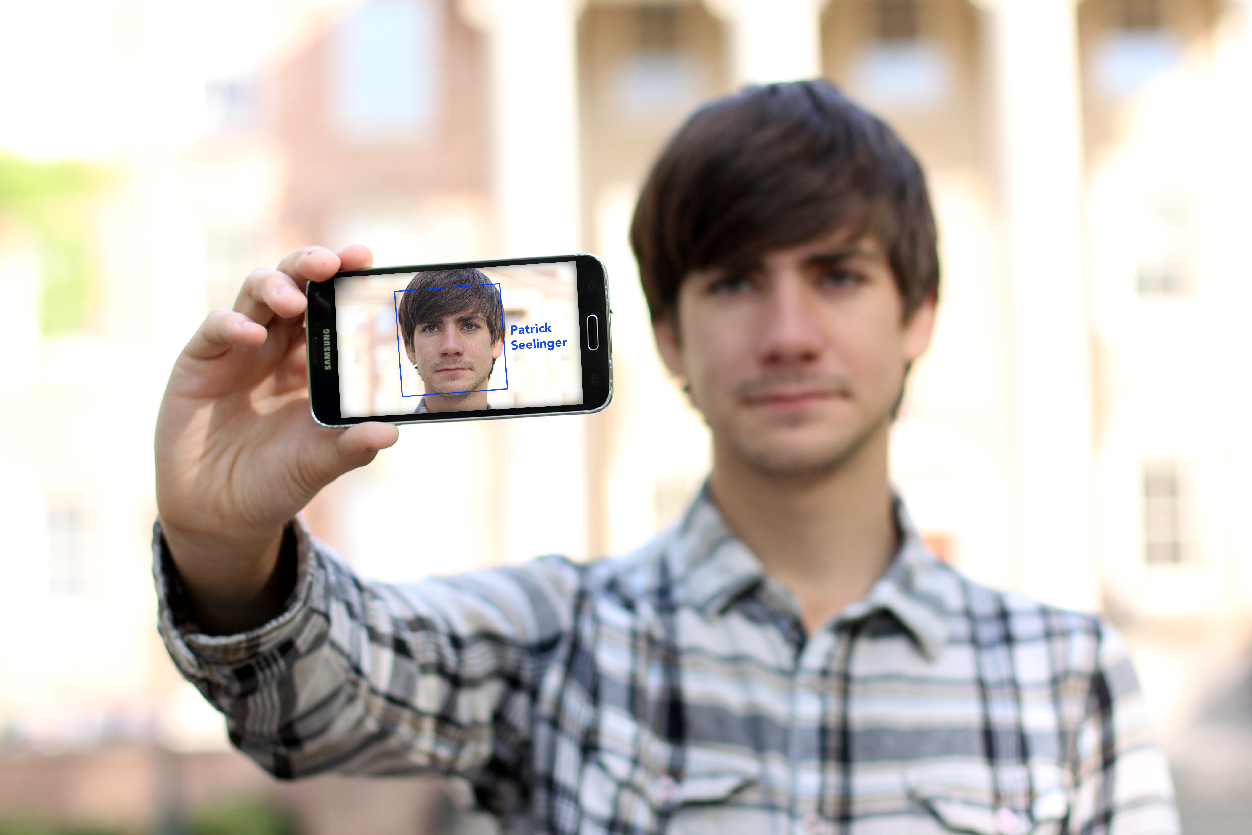 Patrick Seelinger holds up his phone, which shows a depiction of the projected interface for the facial recognition app he's developing. Users will be able to point their phones at a person's face and then tap on the square surrounding it to acquire additional information about that person.