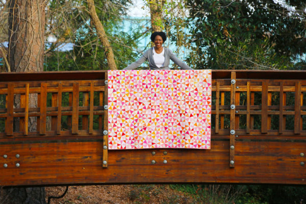 an African-American woman stands on a bridge with a pink and orange, patterned quilt she made