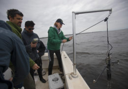A student stands next to the edge of the boat and uses a pulley system to raise a metal instrument from the estuary water.