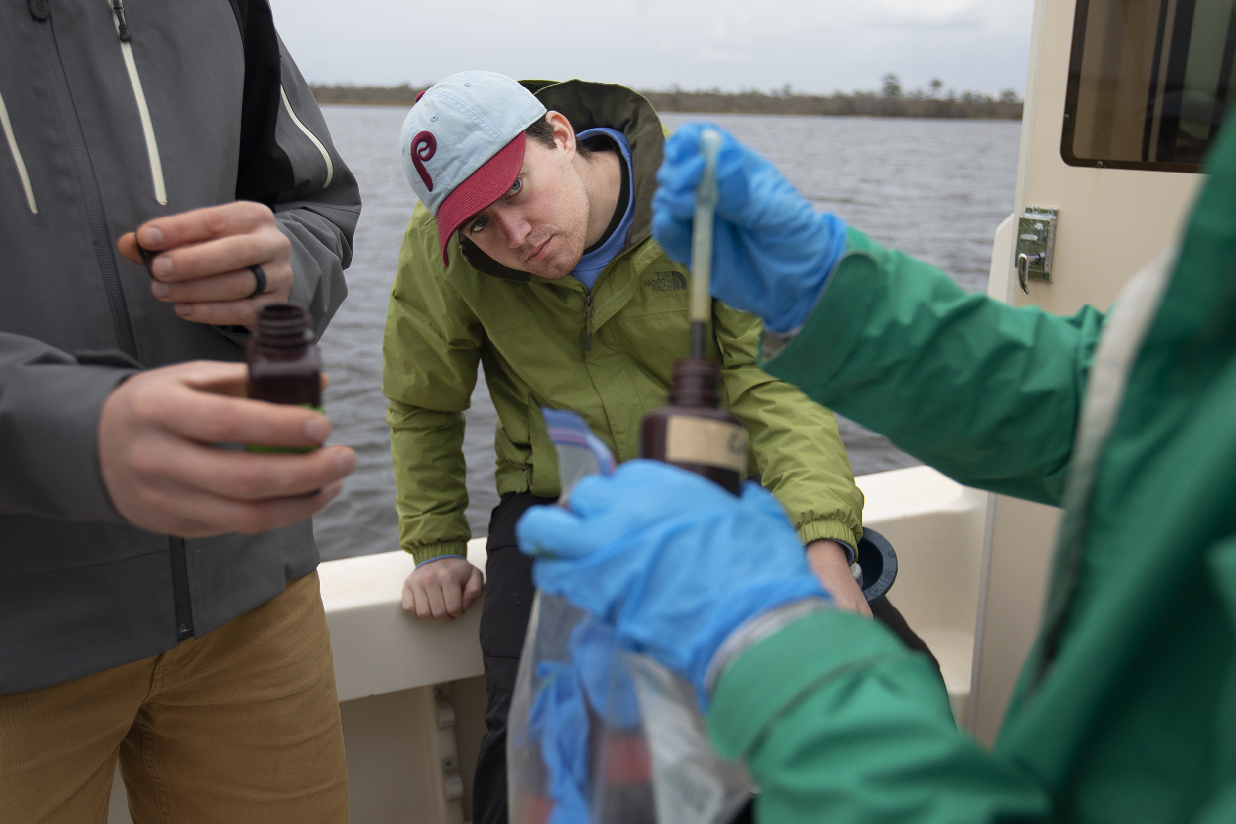 A student sits on the side of the boat and watches as two classmates use droppers to put a solution from one small bottle to another.