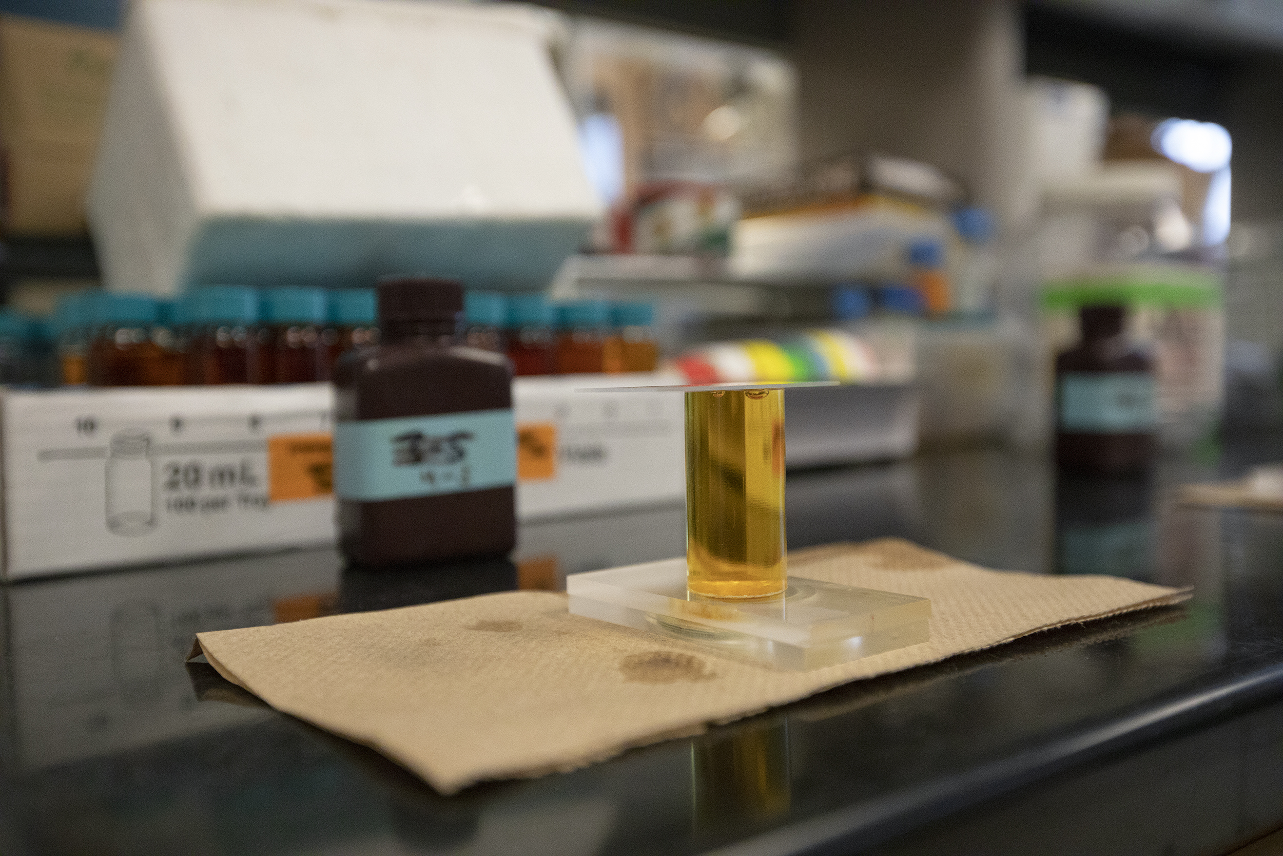 A clear cylinder filled with yellow liquid sits on a laboratory work station table.