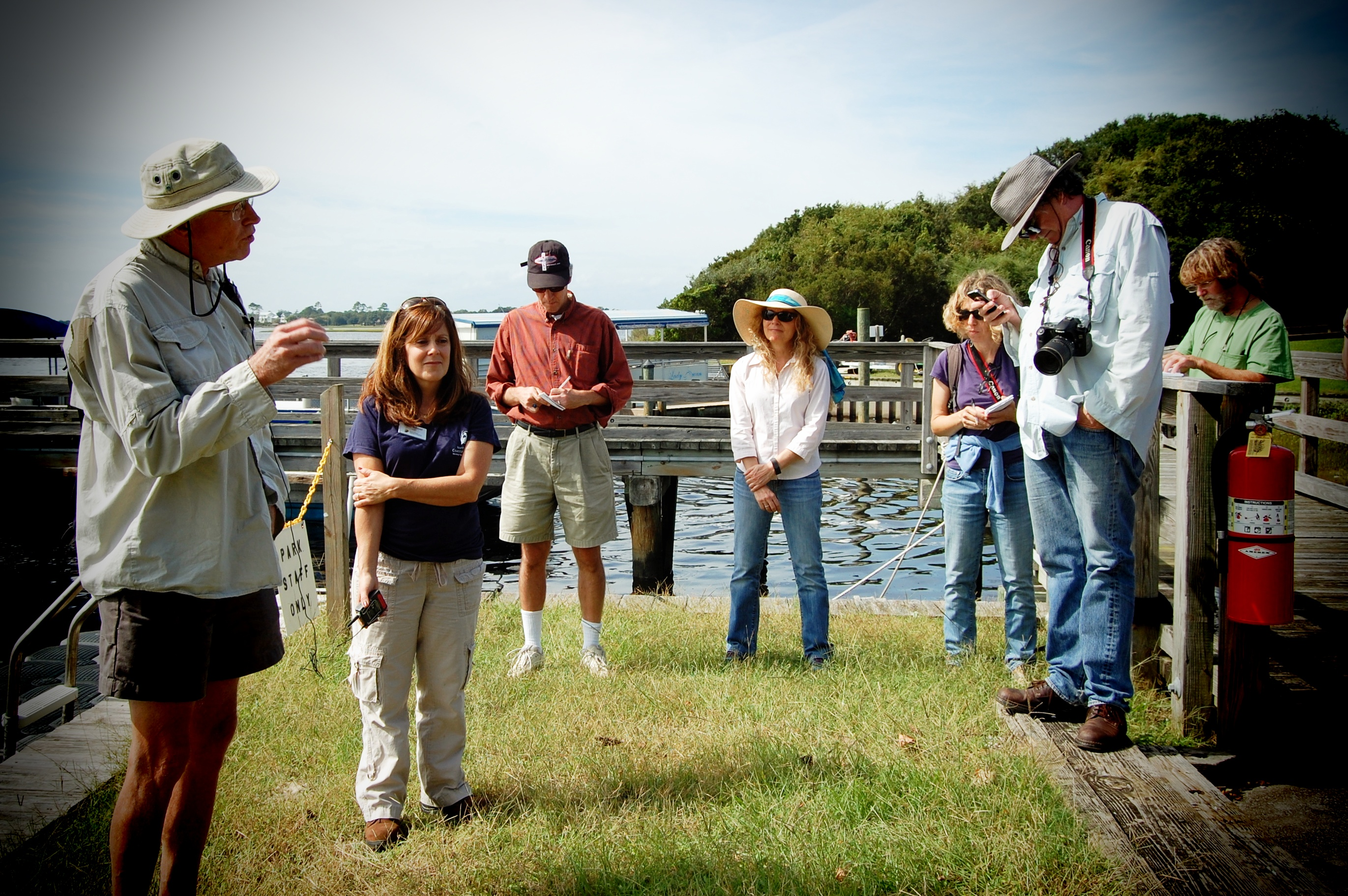 Pete Peterson talks to a group of people by the water in Beaufort