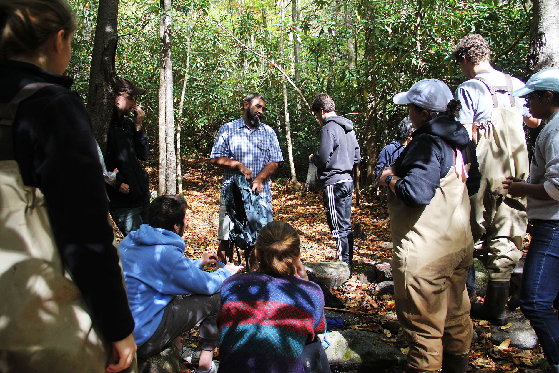 a group of students gather in a circle in the woods
