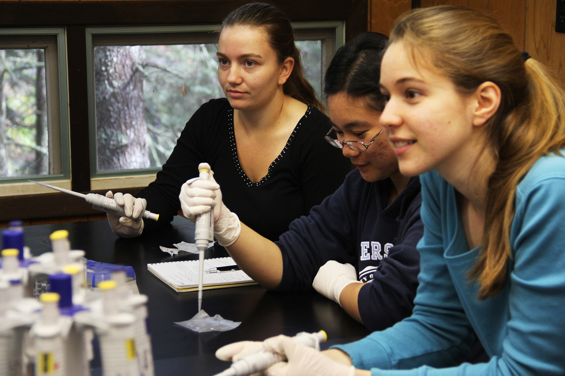 students practice pipetting while listening to Apodaca's instructions