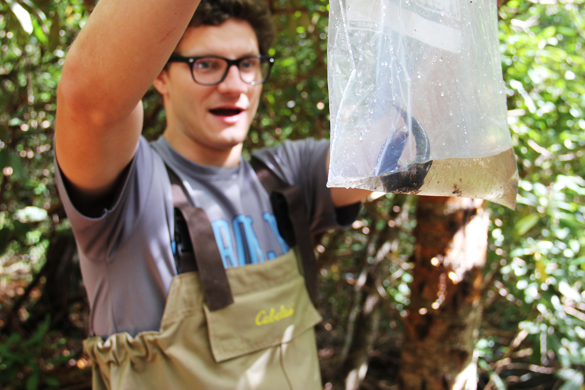 a male student wearing tan Cabela's waders proudly holds up a bag with a blackbelly salamander inside