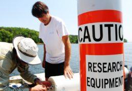 three men lower equipment into lake