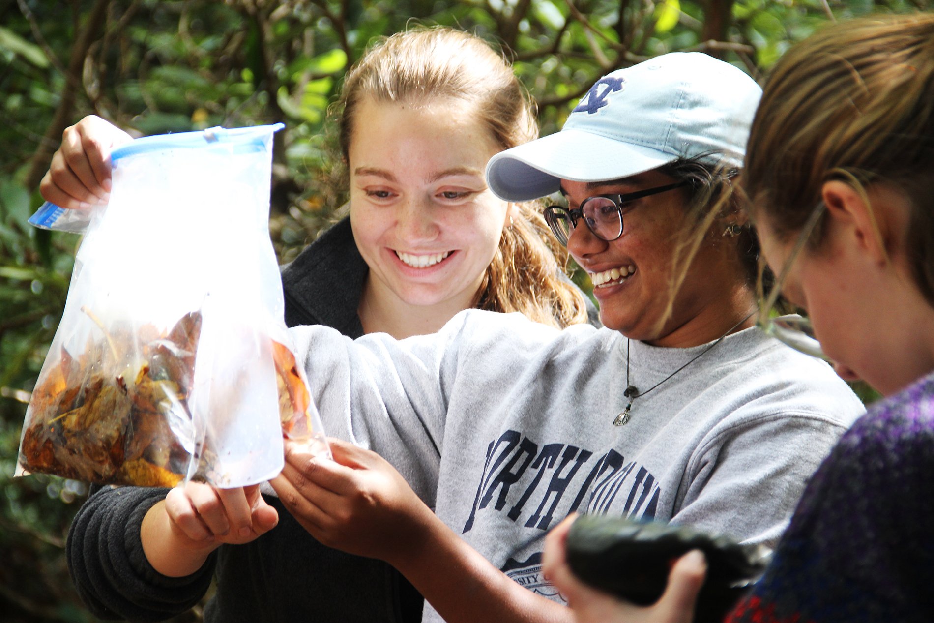 two female students hold up their leaf-filled bags and newly caught salamanders