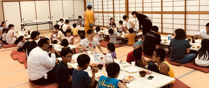 Children and parents sit at tables at a Tenrikyo Community Kitchen