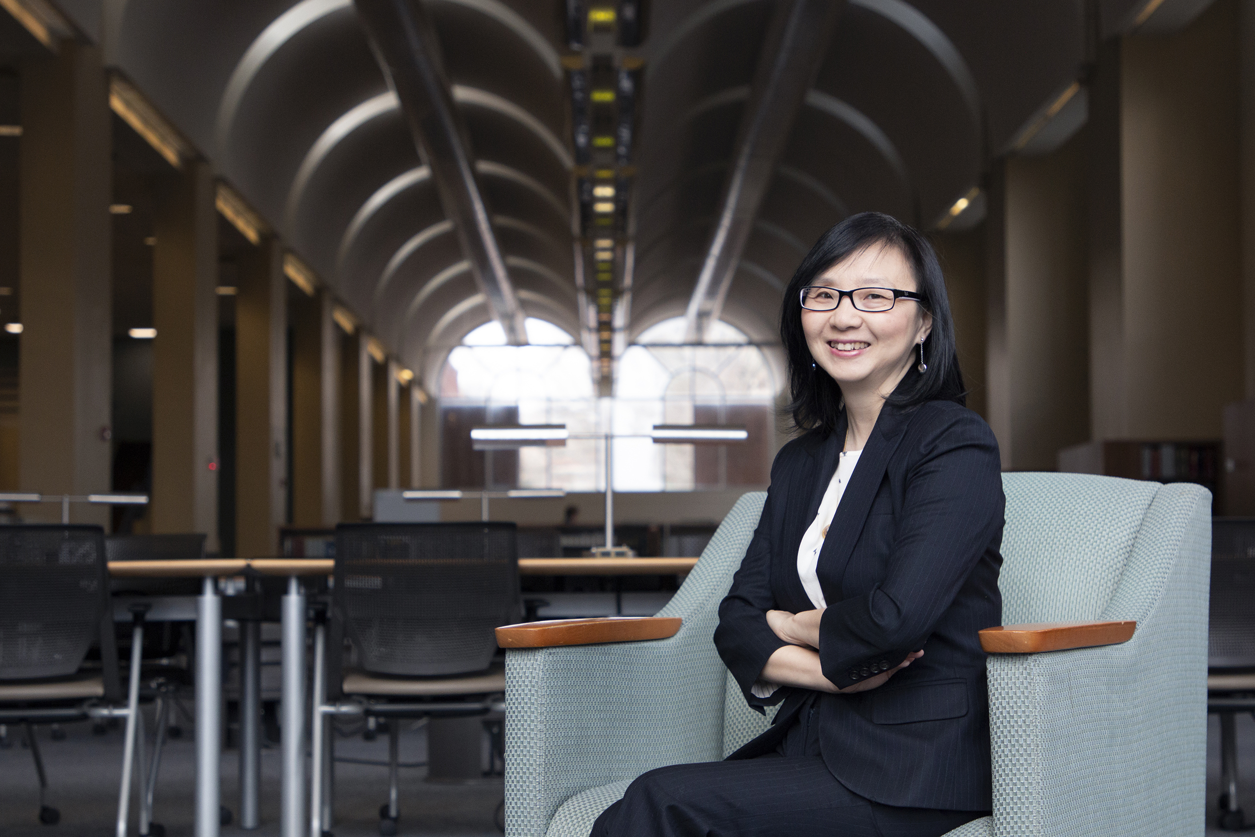 Ping Chen in a blue chair in Davis Library