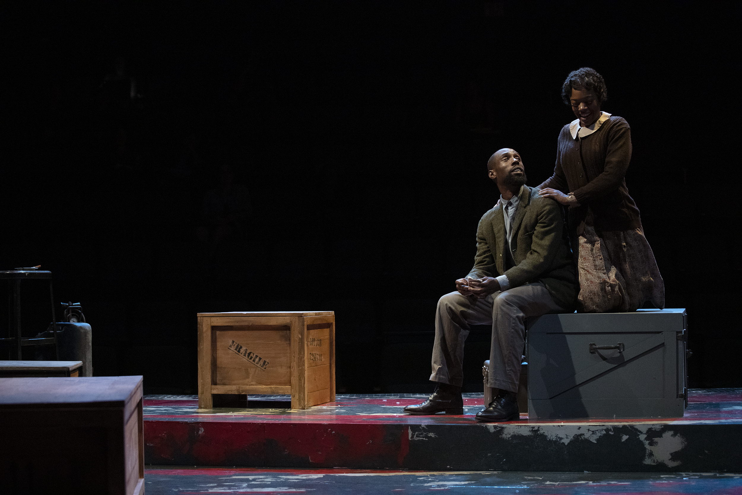 A male and female actor sit on military style crates while talking on stage..