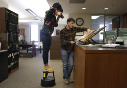 Sarah stands on a library stool while taking a photo of hospital ledgers, held by Lucas in the North Carolina State Archives.
