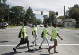 High school students walk through an intersection in Rocky Mount while mapping businesses. Click here to play video.