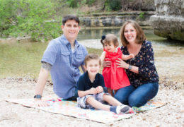 Sandt poses with her husband, son, and daughter for a family photo on a lake shore