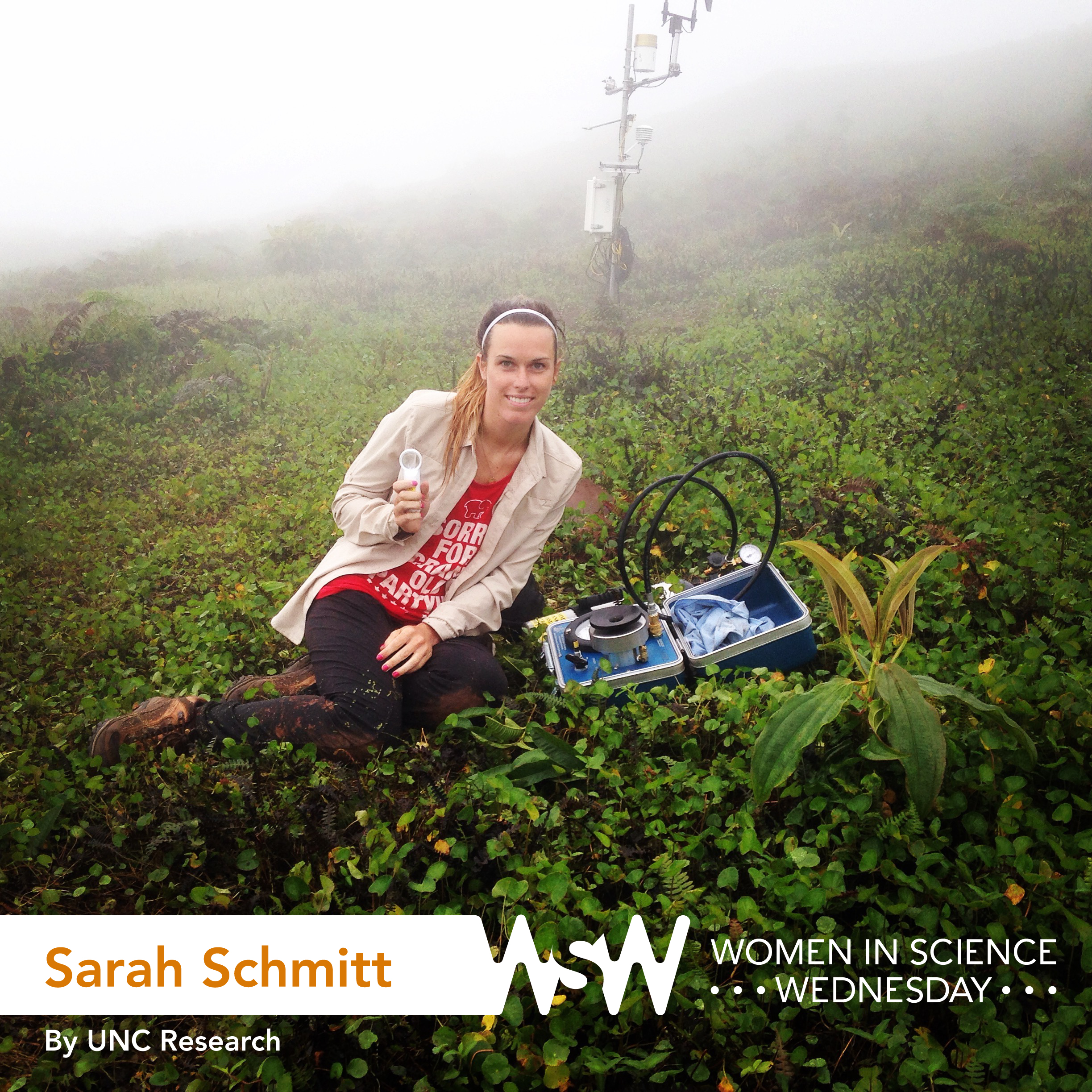 Sarah Schmitt sits in a field with her research equipment, smiling at the camera.