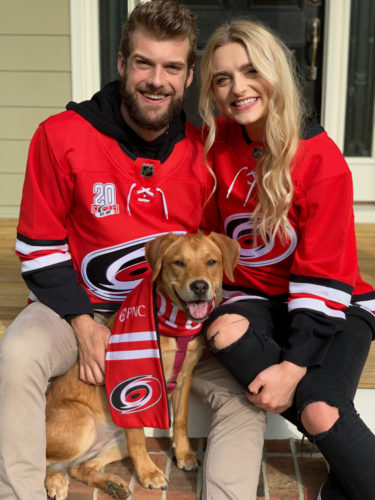 Kevin Pendergast, Makayla Hamrick, and a golden lab wearing Carolina Hurricanes gear