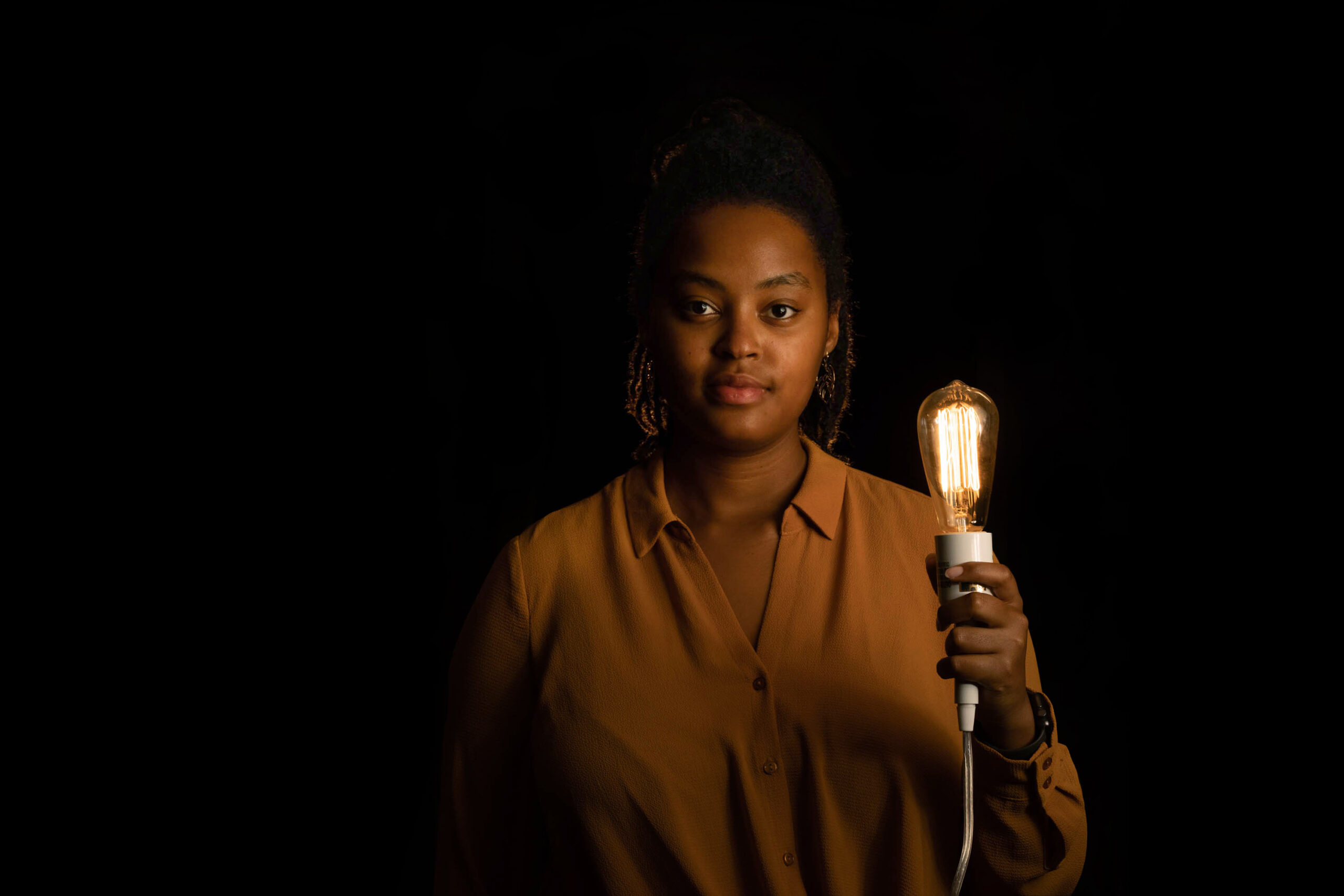 A woman poses for a portrait holding a lightbulb