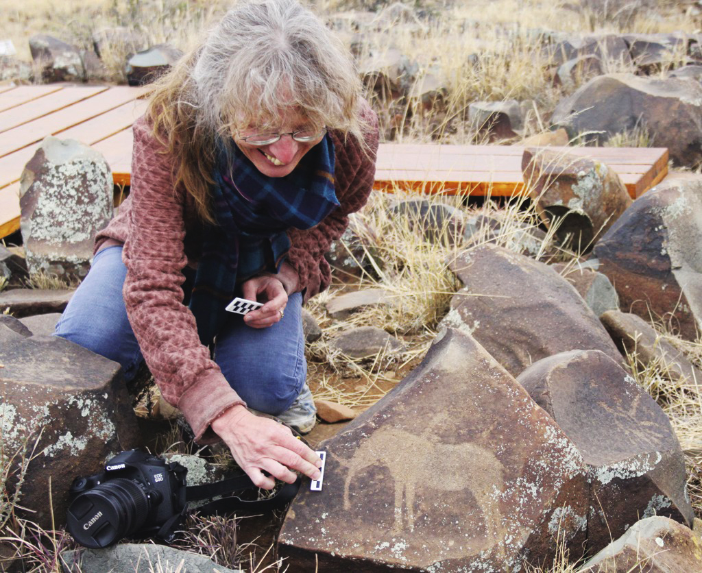 Silvia Tomášková measures an elephant engraving, preparing to take pictures.