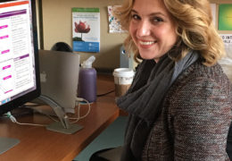 Photo of Stephanie Zerwas posing at her computer with a smile.