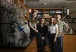 A mother, father, and two daughters pose for a portrait inside a university laboratory space.
